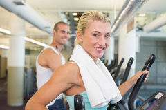 Fit young couple working on x-trainers at gym Royalty Free Stock Photo