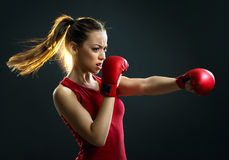 Fit, young, energetic woman boxing, black background Royalty Free Stock Photography