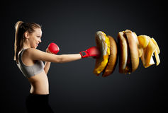 Fit, young, energetic woman boxing unhealthy food