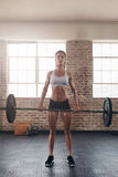 Fit young female athlete lifting heavy weights Royalty Free Stock Photos