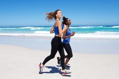 Fit young female friends exercising on the beach Stock Images