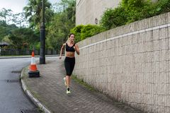 Fit young female jogger jogging on sidewalk in suburban area. Pretty girl working out outdoors. royalty free stock images