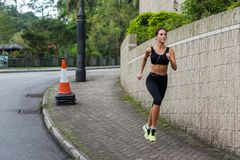 Fit young female jogger jogging on sidewalk in suburban area. Pretty girl working out outdoors. stock photography