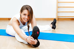Fit young female stretching on the floor sitting on mat Royalty Free Stock Image