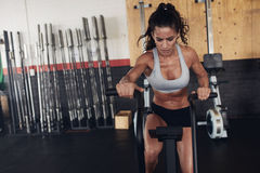 Fit young female working out on gym bike Stock Photography