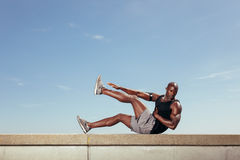 Fit young guy doing stretching workout Royalty Free Stock Image