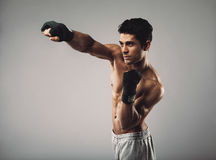 Fit young guy shadowboxing on grey background stock photo