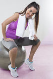 Fit young lady with exercise ball and white towel Stock Image
