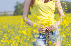 Fit young lady standing among yellow blooming field Royalty Free Stock Photography