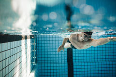 Fit young male swimmer training in the pool. Pro male swimmer in action inside swimming pool Stock Photo