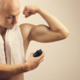 Fit young man applying antiperspirant spray deodorant Stock Images