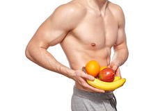 Fit young man with beautiful torso holding fruit Royalty Free Stock Images