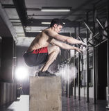 Fit young man box jumping at a crossfit gym.Athlete is performin stock image
