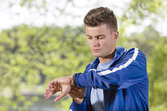 Fit young man checking time at park Royalty Free Stock Photos