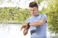 Fit young man checking time at park Royalty Free Stock Image