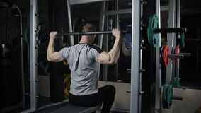 Young muscular man trains in gym. Fit young man doing exercise on smith machine