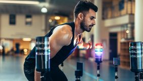 Athlete using a visual stimulus system. Fit young man doing hand eye reaction training with lights sensors in sports lab. Male athlete optimizing the balance Royalty Free Stock Image