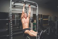Fit young man doing leg raises on a pull up bar.  stock photography