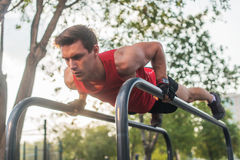 Fit young man doing push ups on horizontal bar outdoors.  Royalty Free Stock Photography
