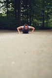 Fit young man doing push ups in a park Stock Image