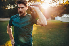 Fit young man exercising with kettlebell in park Royalty Free Stock Image