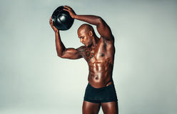 Fit young man exercising with medicine ball. Shot of young fit man exercising with medicine ball. African male stretching with a medicine ball on grey background Stock Image