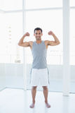 Fit young man flexing muscles in fitness studio Royalty Free Stock Photo