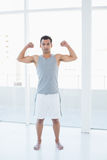 Fit young man flexing muscles in fitness studio Royalty Free Stock Photos