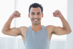 Fit young man flexing muscles in fitness studio Royalty Free Stock Image