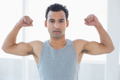 Fit young man flexing muscles in fitness studio Stock Photo
