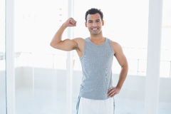 Fit young man flexing muscles in fitness studio Stock Photography