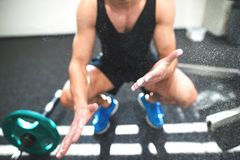 Fit young man in gym with barbells smearing his hands with magnesium. royalty free stock images