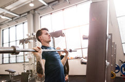 Fit young man in gym working out, lifting barbell Royalty Free Stock Photography