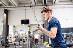 Fit young man in gym working out on pull-down machine. Stock Images