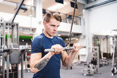 Fit young man in gym working out on pull-down machine. Stock Photography