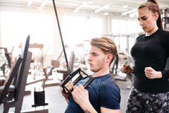 Fit young man in gym working out on pull-down machine. Royalty Free Stock Photography