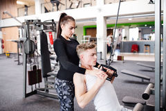 Fit young man in gym working out on pull-down machine. Royalty Free Stock Images