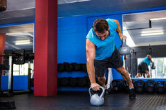 Fit young man holding kettlebells in gym Royalty Free Stock Photo