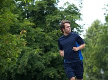 Fit young man jogging outdoors Royalty Free Stock Photos