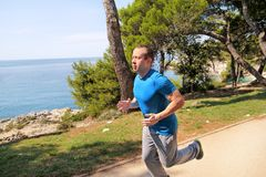 Fit young man jogging on a running trail along seashore. Recreational fitness athlete in sportswear enjoys physical activities. Fit young man jogging on a Stock Photo