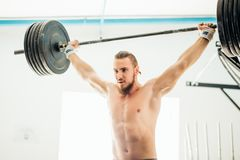 Brutal muscular man with beard train with barbell raised over head in gym. Fit young man lifting barbells looking focused, working out in a gym Stock Images