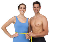 Fit young man measuring womans waist Stock Images