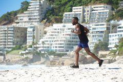 Fit young man running on the beach Royalty Free Stock Image