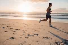 Fit young man running on the beach. Side view shot of fit young man running on the beach in morning. Healthy male model jogging on the sea shore Royalty Free Stock Image