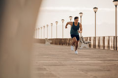 Fit young man running fast on the promenade. Full length shot of fit young man running fast on the promenade. Male runner sprinting in morning stock photos