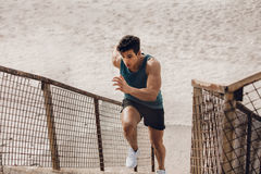 Fit young man running up the steps at beach Stock Images