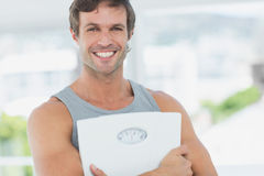 Fit young man with scale in bright exercise room Stock Image