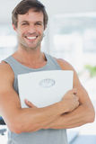 Fit young man with scale in bright exercise room Stock Images