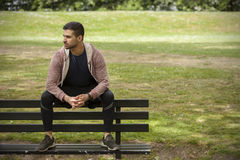 Fit Young Man Sitting on Bench in Park Stock Photography