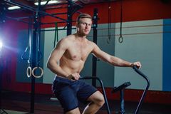 Fit young man using exercise bike at the gym. Fitness male using air bike for cardio workout at cross training gym. Stock Photo